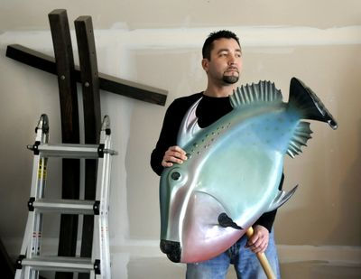 Michael Larsen has been an industrial sculptor for the past 13 years. He holds his triggerfish creation made from fiberglass and foam core.  (Dan Pelle)