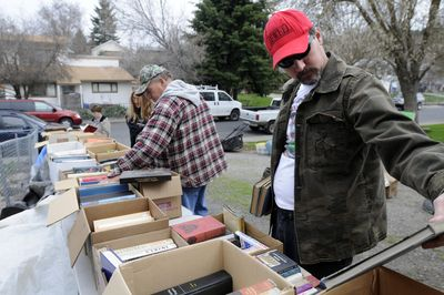 Joel Cummings, right, sorts through books at a garage sale on East Bridgeport Avenue on Friday. Mild spring weather brings shoppers out for bargains.  (Jesse Tinsley / The Spokesman-Review)