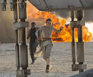 """Daisy Ridley, right, as Rey, and John Boyega as Finn, are shown in a scene from the film, """"Star Wars: The Force Awakens,"""" directed by J.J. Abrams. Early screenings of the film will begin Thursday night. (David James/Disney/Lucasfilm via AP)"""