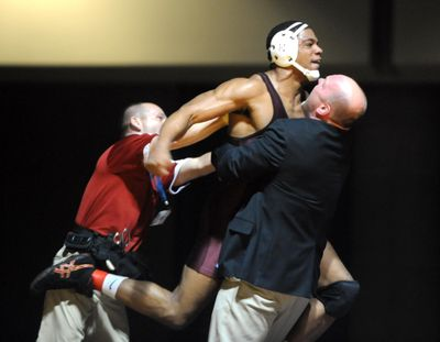 North Idaho College's Jamelle Jones jumps into the arms of his coach, Pat Whitcomb, after pinning Walker Clarke of Labette Community College in the 197-pound class Saturday, Feb. 26, 2011, at the Spokane Convention Center. (Jesse Tinsley / The Spokesman-Review)