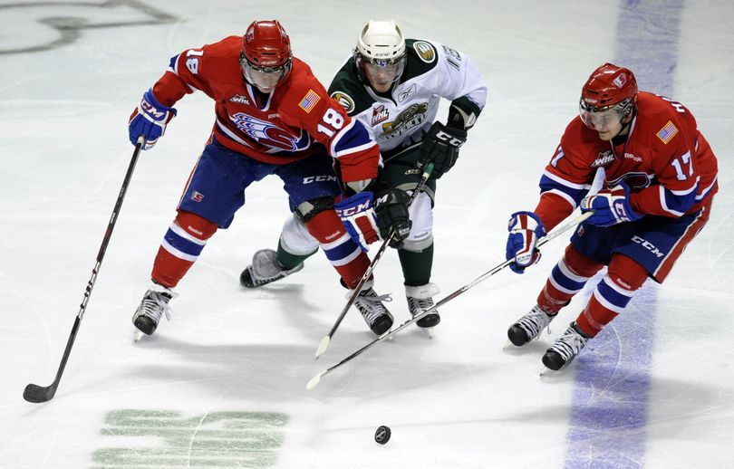 Spokane Chiefs Reid Gow (18) and Mitch Holmberg (17) get to the puck before Everett's Teal Burns Wed., Dec. 14, 2011, in the Spokane Arena. (Colin Mulvany / The Spokesman-Review)