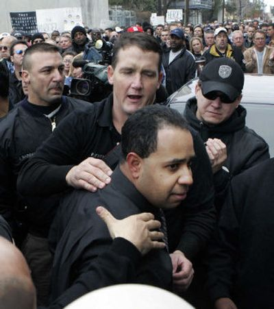 New Orleans police Officer Robert  Barrios, charged with attempted first-degree murder, is escorted through a crowd of supporters  as he arrives at the city jail in New Orleans on Tuesday.   (Associated Press / The Spokesman-Review)