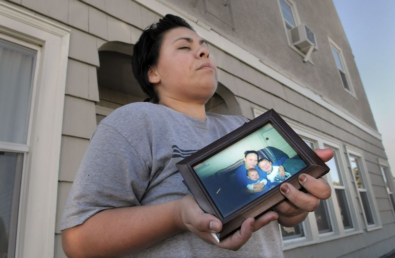 Angela Gilbert struggles to hold back tears as she stands outside a Hillyard apartment building holding a photo of her sister, Rebecca McCollough and her children, Wednesday Sept. 29, 2010. Police say McCollough's 1-year-old son Santiago was beaten to death by her boyfriend Tuesday night. (Christopher Anderson / The Spokesman-Review)