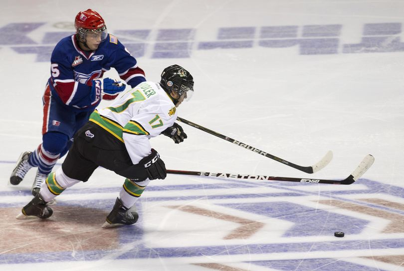 Spokane Chiefs Tanner Mort (5) and Prince Albert's Todd Fiddler chase the puck in the second period, Friday, Oct. 14, 2011, in the Spokane Arena. (Colin Mulvany / The Spokesman-Review)