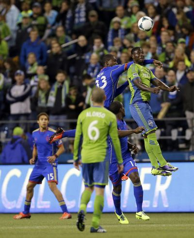 Seattle's Eddie Johnson, right, leaps for a header in front of Colorado's German Mera in first- half action on Wednesday. (Associated Press)