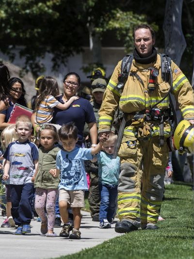 Firefighters and sheriff's deputies escort children from Academy on the Hill pre-k school in Aliso Viejo, Calif, on Tuesday, May 15, 2018, after a fatal explosion nearby. (Mindy Schauer / Associated Press)