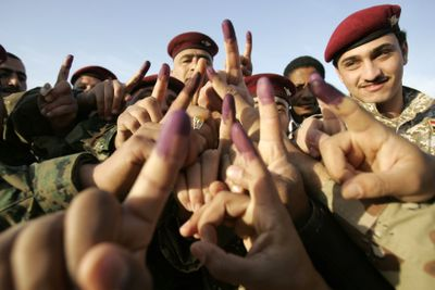 Iraqi soldiers display their ink-stained fingers after casting their votes Wednesday in Najaf, Iraq.  (Associated Press / The Spokesman-Review)