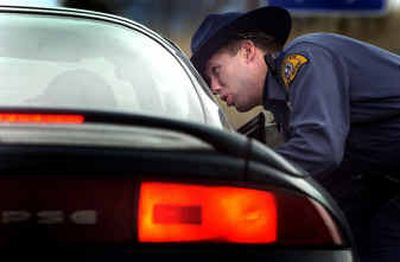 Trooper Travis Robbins, of the Washington State Patrol, talks to a driver about speeding through the eastbound side of the construction zone on Interstate 90 Friday afternoon. The driver wasn't ticketed.    (Brian Plonka / The Spokesman-Review)