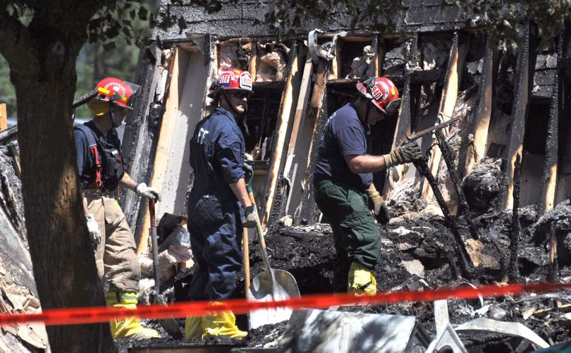 Members of the Fire District 9 Fire Investigation Task Force comb through the rubble of a destroyed Chattaroy mobile home on Thursday, July 18, 2013. The mobile home was destroyed July 17 in an explosion sheriff's deputies are investigating as either an attempted murder or a high-level assault. A man and woman both suffered severe burns in the blaze and were transferred to Harborview Medical Center in Seattle. (Kaitlin Gillespie / The Spokesman-Review)