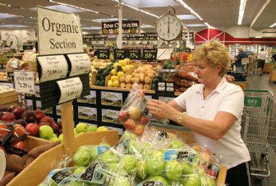 Dorothy Robinson of Scottsdale, Ariz., checks the organic apples at Sprout's in Scottsdale. Organic products have a tiny slice, about 2.5 percent, of the nation's food market, but the slice is expanding at a feverish pace with demand outstripping supply.   (Associated Press / The Spokesman-Review)