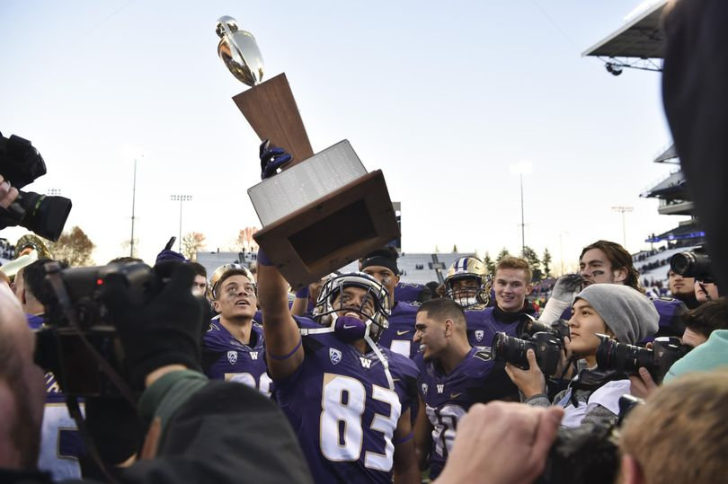 Washington receiver Neel Salukhe (83) hoists the Apple Cup trophy after defeating WSU on Friday, Nov 27, 2015, at Husky Stadium in Seattle, Wash. (Tyler Tjomsland / The Spokesman-Review)