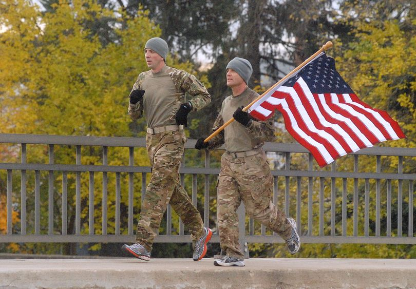 Les Rose, left, and Jay Via, who served in Afghanistan at different times, decided to run more than 13 miles with an American flag, Monday, Nov. 11, 2013 in Troy, Ohio.