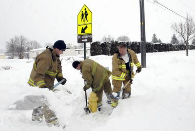 Spokane Valley Fire Department firefighter Matt Brodsky, Capt. Mike Charter and firefighter Jim Mulena dig out a hydrant Monday. (J. BART RAYNIAK / The Spokesman-Review)