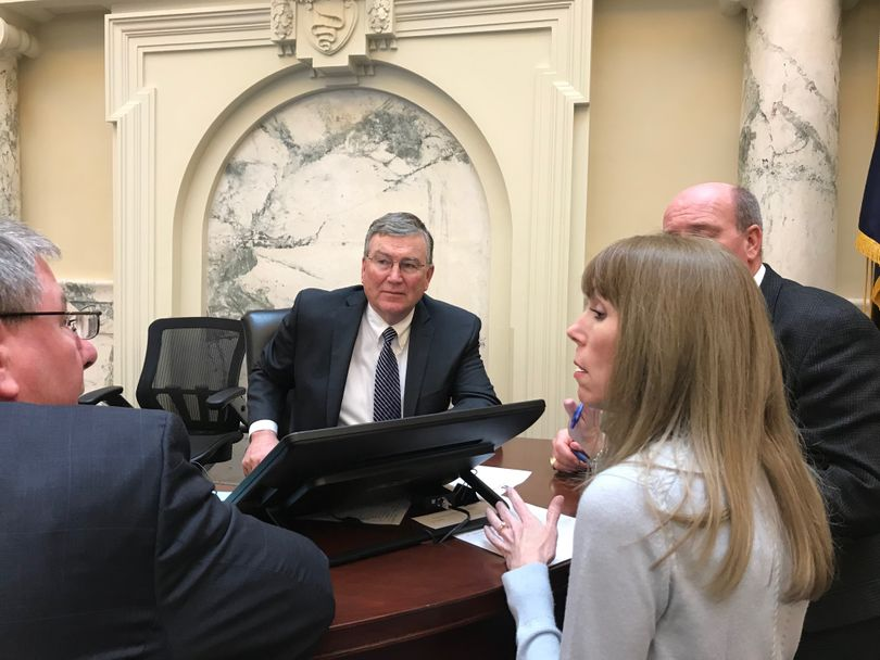House Speaker Scott Bedke, center, confers with Rep. Lynn Luker, left, House chief clerk Carrie Maulin, and House Majority Leader Mike Moyle, right, on technical questions about how the House will end its session this year, on Wednesday, March 22, 2018; lawmakers are hoping to adjourn this year's session by Friday. (The Spokesman-Review / Betsy Z. Russell)
