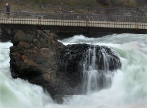A passer-by takes in the falls at Riverfront Park in spring 2008  in Spokane.  The falls are central to the region's history.  (File / The Spokesman-Review)