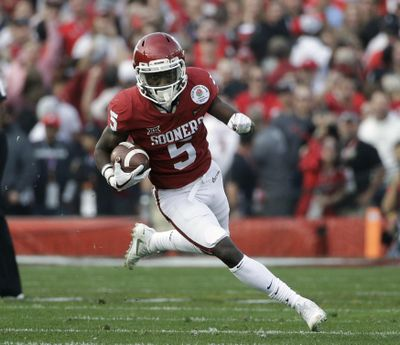 """In this Jan. 1, 2018, file photo, Oklahoma wide receiver Marquise Brown carries the ball during the Rose Bowl NCAA college football game against Georgia, in Pasadena, Calif. Marquise """"Hollywood"""" Brown made his mark last season as a speedster. Now that he's added tools and size in the offseason, he expects to be even more dangerous. He gained more than 1,000 yards receiving last season, and now, the junior is looking for more. He'll be a marked man when the seventh-ranked Sooners open on Sept. 1 against Florida Atlantic. (Jae C. Hong / Associated Press)"""
