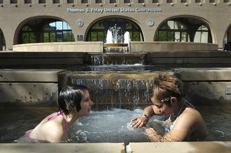 Andy Christensen (cq), left, 15, and Marche Osborne (cq), 14, cool off from 90-degree heat in the Thomas S. Foley federal courthouse fountain in downtown Spokane after school Wednesday afternoon, May 17, 2006.  More record-breaking temperatures are expected this week.  Holly Pickett The Spokesman-Review (Holly Pickett / The Spokesman-Review)