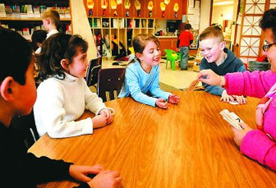 Kindergarteners Ava McClintock, center, Mykael Maddox, center right, try to name letters and sounds on cards held by teacher Jacque Dean, right, in the all-day kindergarten class at Atlas Elementary in Hayden. At left are Emigdio Guzman-Contreras and Tayler Holbert, second from left. For kids who need reading and language help, the all-day kindergarten reinforces what half-day kindergarteners are learning.   (Jesse Tinsley / The Spokesman-Review)