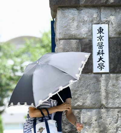 A woman walks past the gate of Tokyo Medical University on Aug. 2, 2018. The Japanese medical university's alleged systematic deduction of entrance exam scores only from female applicants has sparked outrage across Japan and invited criticisms from Cabinet officials. The scandal surfaced after the Yomiuri newspaper reported Thursday that Tokyo Medical University has been slashing female applicants entrance exam scores for years to keep female student population low, on grounds they tend to quit as doctors after starting families, causing staffing shortages. (Ayaka Aizawa / Kyodo News)