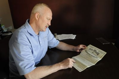 Farmers Insurance agent David Boley looks at a 1940 insurance policy written on a man who recently died. It was a whole life policy that matured in the 1970s and had a face value of $1,000. Because of interest, it will pay around $2,800.  (Jesse Tinsley / The Spokesman-Review)