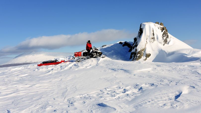 Josh Rindal of Spokane comes by a unique rock uplift on the Iditarod Trail with Little McKinley in the background. Rindal and Bob Jones of Kettle Falls were snowmobiling 1,400-miles along the route of Alaska's famous Iditarod Sled Dog Race in March 2014. (Robert Jones)