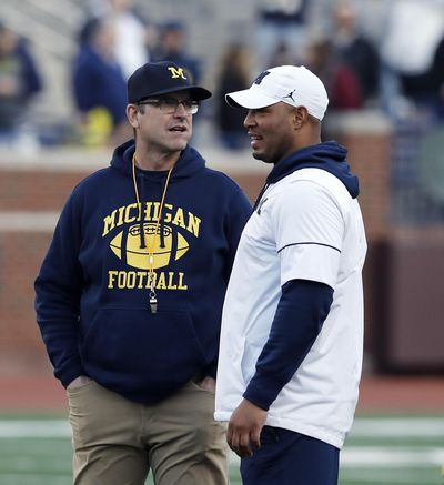 In this April 13, 2019 photo Michigan head coach Jim Harbaugh, left, and offensive coordinator Josh Gattis talk during the team's annual spring NCAA college football game in Ann Arbor, Mich. Harbaugh seems to be set up for success at Michigan in his fifth season, leading a program that is a popular choice to win the Big Ten. (Carlos Osorio / Associated Press)