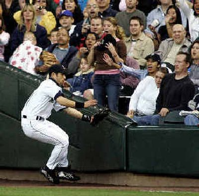 Mariners right fielder Ichiro Suzuki goes to the wall to snag a fly ball in foul territory in the third inning at Safeco Field.  (Associated Press / The Spokesman-Review)