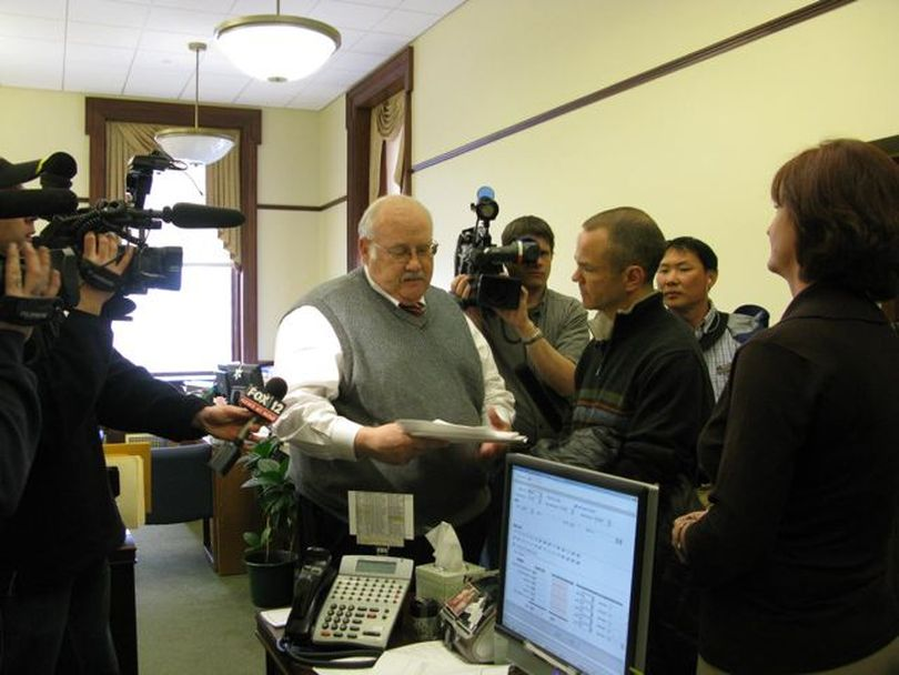 Secretary of State Ben Ysursa, center, accepts petitions Friday from Mike Lanza, center right, to launch a referendum drive to overturn SB 1184, the third school-reform bill; paperwork already has been approved to attempt a challenge to the two earlier school reform bills in the same manner. (Betsy Russell)