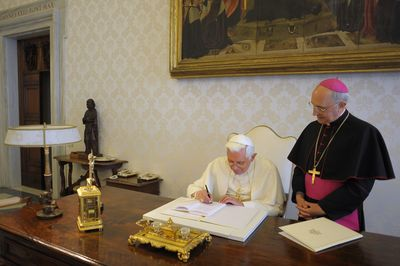 In this photo provided by the Vatican newspaper L'Osservatore Romano, Pope Benedict XVI signs his third encyclical of his pontificate as his Archbishop James Harvey looks on at the Vatican on Monday. (Associated Press / The Spokesman-Review)