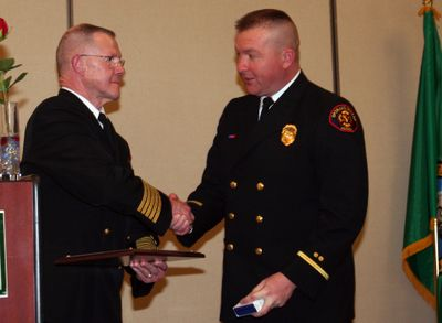 Fire Chief Mike Thompson congratulates Deputy Fire Marshal Rick Freier as he receives the department's Medal of Valor.  Courtesy of the Spokane Valley Fire Department (Courtesy of the Spokane Valley Fire Department / The Spokesman-Review)
