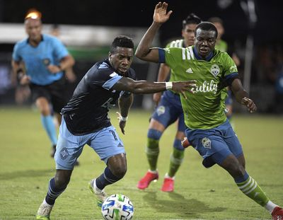 Vancouver Whitecaps forward Cristian Dajome, left, and Seattle Sounders defender Nouhou Tolo compete for a ball during the second half of an MLS soccer match, Sunday, July 19, 2020, in Kissimmee, Fla.  (Associated Press)