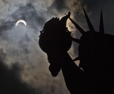 A partial solar eclipse appears over the Statue of Liberty on Liberty Island in New York, on Monday, Aug. 21, 2017. (Associated Press)