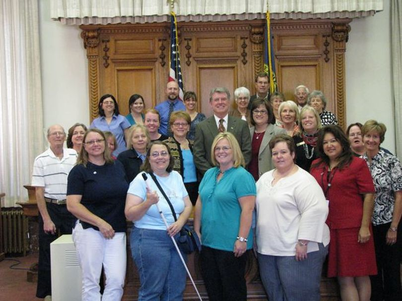 Gov. Butch Otter poses with advocates of community volunteerism after signing a commemorative proclamation for a