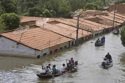 People travel by boat in a flooded street in Trizidela do Vale, Brazil, on Saturday.  (Associated Press / The Spokesman-Review)