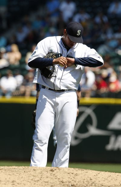 Felix Hernandez looks at his wrist after being hit by a ball. (Associated Press)