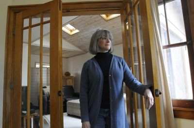 Merry Armstrong stands between a pair of French doors installed by a contractor she hired to make improvements to her 1929 home. The contractor remodeled a Jacuzzi room into the den behind her and helped her oversee work by other contractors.  (Jesse Tinsley / The Spokesman-Review)