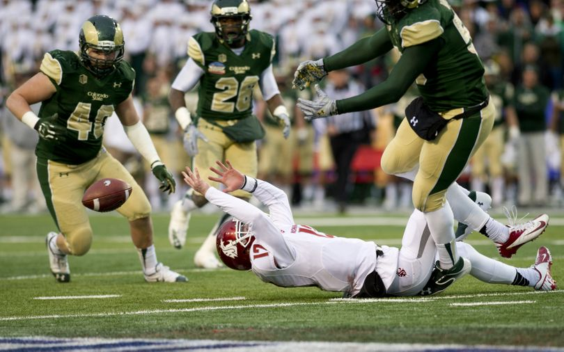 Washington State quarterback Connor Halliday loses control of the ball against Colorado State in a play that officials initially ruled a fumble recovered by CSU, but was retracted during the second half of the Gildan New Mexico Bowl on Saturday, Dec. 21, 2013, at University Stadium in Albuquerque, New Mexico. Colorado State won the game 48-45. (Tyler Tjomsland / The Spokesman-Review)