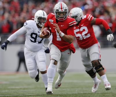 Ohio State quarterback Justin Fields, center, runs for a first down against Penn State during the first half of an NCAA college football game Saturday, Nov. 23, 2019, in Columbus, Ohio. (Jay LaPrete / Associated Press)