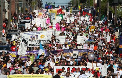 Participants walk down South Jackson Street during a May Day march through downtown Seattle on Friday.  (Associated Press / The Spokesman-Review)