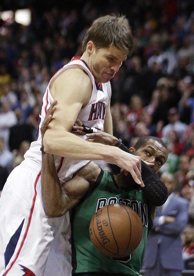 Rajon Rondo, right, injured his knee Friday against the Hawks. (Associated Press)