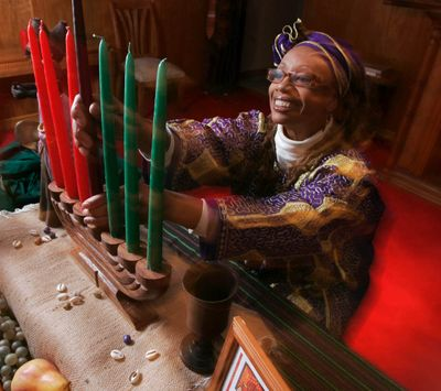 Ruth Ndiagne Dorsey arranges a Kwanzaa setting for a media photo at her church, The Shrine of the Black Madonna, in Atlanta. (Associated Press)
