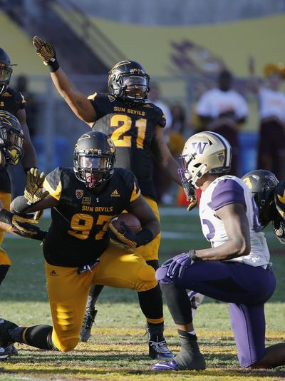 Arizona State's Edmond Boateng, left, comes up with the football after a fumble by Washington's Joshua Perkins, right, during the Huskies' fourth-quarter collapse last season in Tempe, Arizona. (Ross D. Franklin / Associated Press)