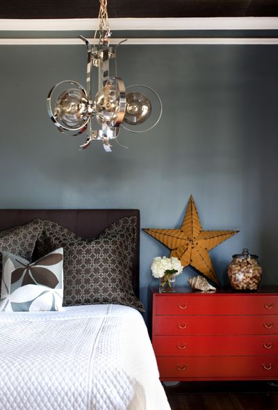Designer Brian Patrick Flynn pairs a new headboard and bedding with an inherited antique Asian-style chest and retro modern pendant, accessorized with natural and rustic items collected over the years. (The Spokesman-Review)