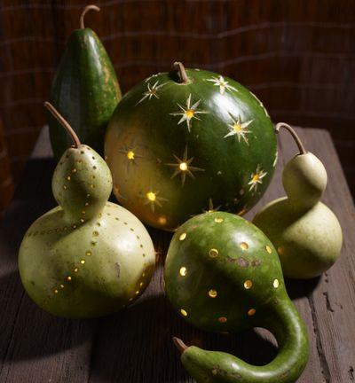 Better Homes and Gardens suggests drilling gourds and pumpkins with holes, then inserting battery-operated votives. (Associated Press)