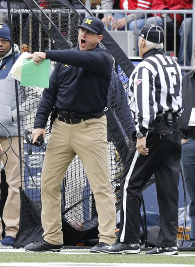 Michigan head coach Jim Harbaugh, left, yells at the field judge during the first half of an NCAA college football game against Ohio State, Saturday, Nov. 26, 2016, in Columbus, Ohio. Ohio State beat Michigan 30-27 in double overtime. (Jay LaPrete / Associated Press)