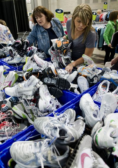 After picking up their Bloomsday race packets, Virginia Ramshaw, left, and her daughter Rachel rummage through bins of running shoes at the trade show Friday in the Group Health Exhibit Hall.  (Colin Mulvany / The Spokesman-Review)