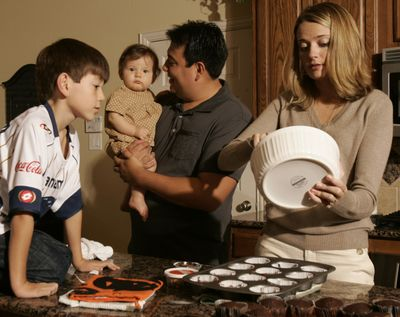 Nicholas Odria, from left to right, Ava Odria, Mark Odria and Katelyn Odria make cupcakes in their kitchen in their Texas home. (Associated Press)