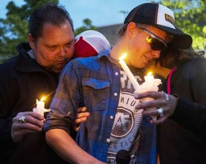 Cody Fowler, center, who grew up with Leo C. Neal for many years, is hugged by Leo Neal Sr, left, and Misty Neal during a candlelight vigil held Wednesday night at Post Falls High School. (Loren Benoit/Coeur d'Alene Press photo)