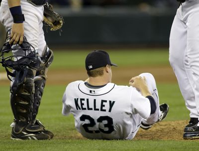 Mariners reliever Shawn Kelley sits on the ground after falling from pain from a strained muscle in the 10th inning. (Associated Press / The Spokesman-Review)