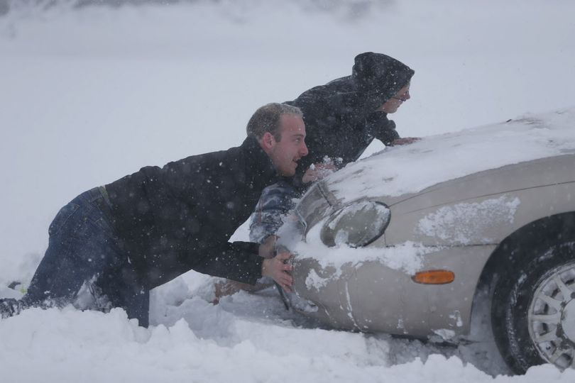 Eric Dehond, left, and Dakota Paciorkowski help push out a stuck motorist on George Urban Boulevard in Depew, N.Y. on Tuesday, Nov. 18, 2014.  Several feet of lake-effect snow paralyzed the Buffalo area Tuesday, forcing state troopers to deliver blankets and other supplies to motorists stranded on the New York State Thruway and adding an ominous note to a wintry season that�s already snarling travel and numbing fingers from the Midwest to the Carolinas. (Derek Gee / Associated Press)